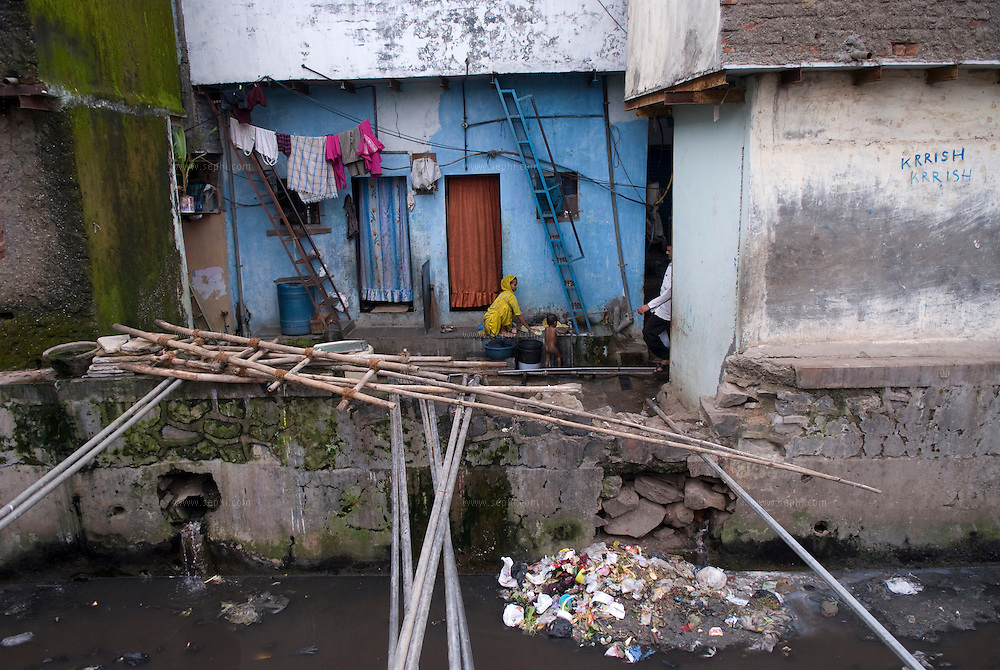 A mother washing cloths while her little baby showers outside their home next to the polluted drainage canal. Dharavi, August 2007