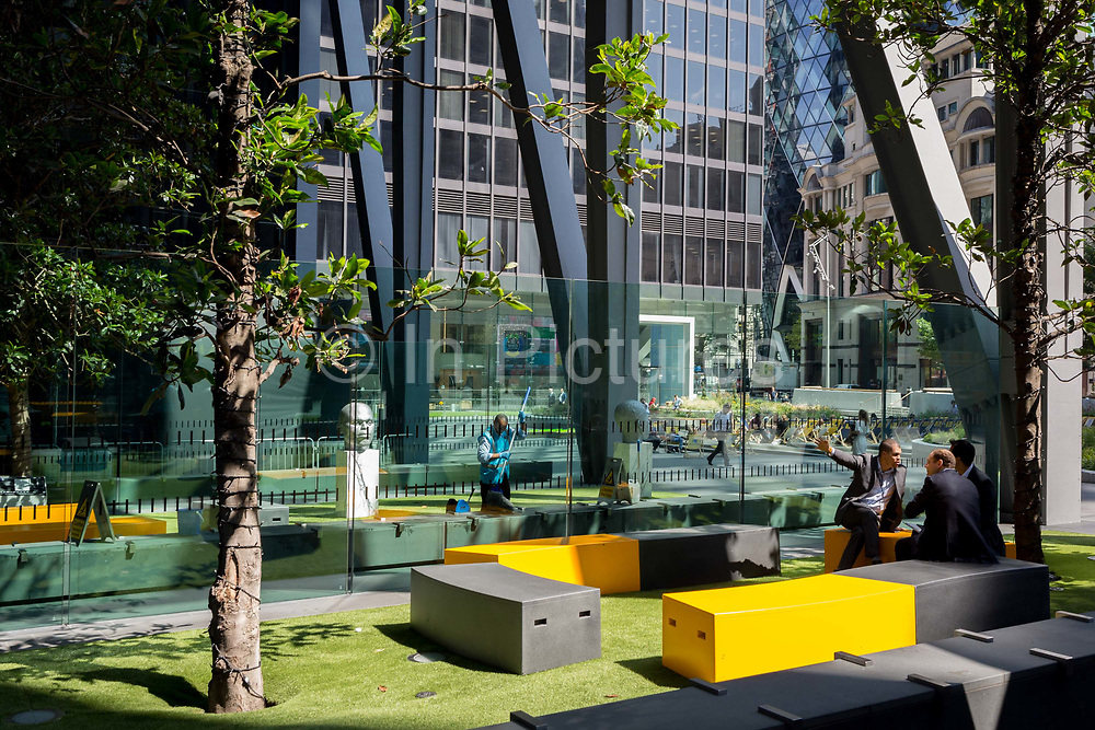 As a contract cleaner sweeps up litter, office workers hold a meeting outside the Leadenhall Buolding during the 2018 heatwave in the City of London, the capitals financial district, on 24th July 2018, in London, England.