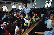 Batak Sunday school for children before mass..Batak Indigenous Christian people living on Samosir Island and nearby Lake Toba in Indonesia. There are some 6 million Christian Batak in Indonesia, the world's largest Muslim country of 237 million people, which has more Muslims than any other in the world. Though it has a long history of religious tolerance, a small extremist fringe of Muslims have been more vocal and violent towards Christians in recent years. ..Batak religion is found among the Batak societies around Lake Toba in north Sumatra. It is ethnically diverse, syncretic, liable to change, and linked with village organisations and the monotheistic Indonesian culture. Toba Batak houses are boat-shaped with intricately carved gables and upsweeping roof ridges, and Karo Batak houses rise up in tiers. Both are built on piles and are derived from an ancient Dong-Son model. The gable ends of traditional houses, Rumah Bolon or Jabu, are richly decorated with the cosmic serpent Naga Padoha carved in wood or in mosaic, lizards, double spirals, female breasts, and the head of the singa, a monster with protruding eyes that is part human, part water buffalo, and part crocodile or lizard. The layout of the village symbolises the Batak cosmos. They cultivate irrigated rice and vegetables. Irrigated rice cultivation can support a large population, and the Toba and the Karo live in densely clustered villages, which are limited to around ten homes to save farming land. The kinship system is based on marriage alliances linking lineages of patrilineal clans called marga. In the 1820's Islam came to the southern Angkola and Mandailing homelands, and in the 1850's and 1860's Christianity arrived in the Angkola and Toba region with Dutch missionaries and the German Rheinische Mission Gesellschaft. The first German missionary caused the Dutch to stop Batak communal sacrificial rituals and music, which was a major blow to the traditional religion. Dutch colonial policy favoured Chr