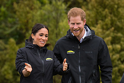 The Duke and Duchess of Sussex react after taking part in a welly wanging contest at a dedication of an area of bush to the Queen's Commonwealth Canopy, in Redvale on the North Shore, on day three of the royal couple's tour of New Zealand.