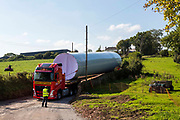 Wind turbine installation. The base of a wind turbine arriving by an exceptional load lorry to Alvington Court Farm, Forest of Dean. Gloucestershire. The truck has rear steering to guide it through small country lanes to arrive at its location ready for construction.