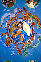 icon of Jesus Christ on a vault in Georgian orthodox church in dominant blue color with inscription in Georgian alphabet