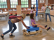 """Fourth grade teacher Mary McDevitt (left) pushes student Daisy Lazaroff, 10, on a wheeled """"rig-a-ma-jig"""" she helped put together at the """"Design Small, Build Big"""" exhibit. The wheeled scooter appears to be the marriage between giant lego blocks and an erector set. The Magic House had two fourth-grade classes from the New City School visit their new permanent satellite location at 5127 Delmar Boulevard in St. Louis, MO on Wednesday May 23, 2019.<br /> Photo by Tim Vizer"""