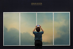 "© Licensed to London News Pictures. 23/07/2020. LONDON, UK. A visitor views ""Wolken (fenster) (Clouds (window)) (1970) by Gerhard Richter, estimate: £9-12 million. Preview of works on display at Sotheby's London ahead of a one-off auction on July 28.  Titled 'Rembrandt to Richter', the sale will offer the very best from Old Masters, Impressionist & Modern Art, Modern & Post-War British Art and Contemporary Art.  The exhibition is open to the public at Sotheby's New Bond Street galleries until July 28. [Image embargoed for release until 9am BST 24 July 2020].  Photo credit: Stephen Chung/LNP"