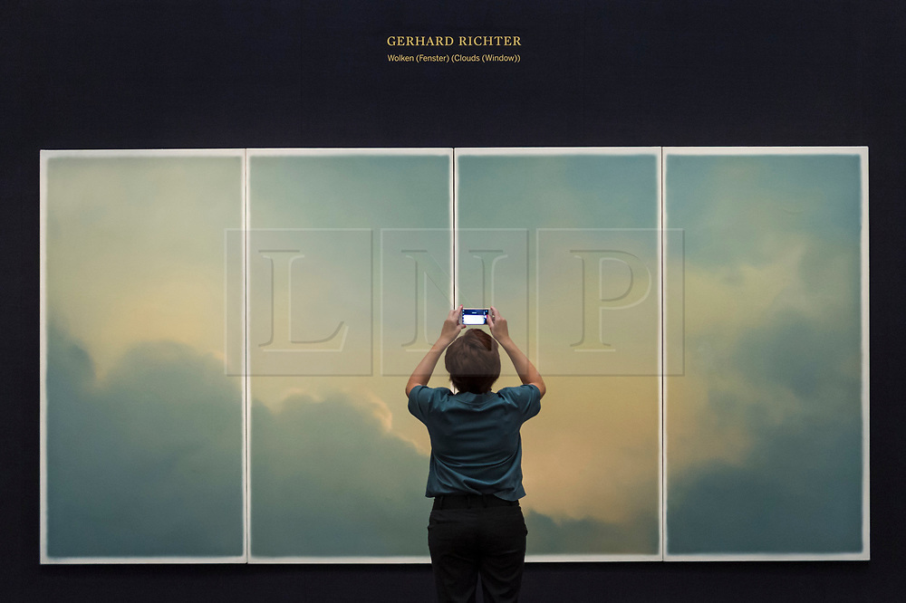 """© Licensed to London News Pictures. 23/07/2020. LONDON, UK. A visitor views """"Wolken (fenster) (Clouds (window)) (1970) by Gerhard Richter, estimate: £9-12 million. Preview of works on display at Sotheby's London ahead of a one-off auction on July 28.  Titled 'Rembrandt to Richter', the sale will offer the very best from Old Masters, Impressionist & Modern Art, Modern & Post-War British Art and Contemporary Art.  The exhibition is open to the public at Sotheby's New Bond Street galleries until July 28. [Image embargoed for release until 9am BST 24 July 2020].  Photo credit: Stephen Chung/LNP"""