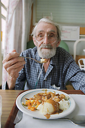 Elderly patient on acute medical admissions ward eating lunch,