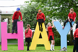 © London News Pictures. 26/05/2016. Hay on Wye, UK. The opening day of the Hay Festival 2016, and pupils from Longtown School in Herefordshire,  have fun with the huge Hay sign on the festival site. Photo credit: Keith Morris/LNP