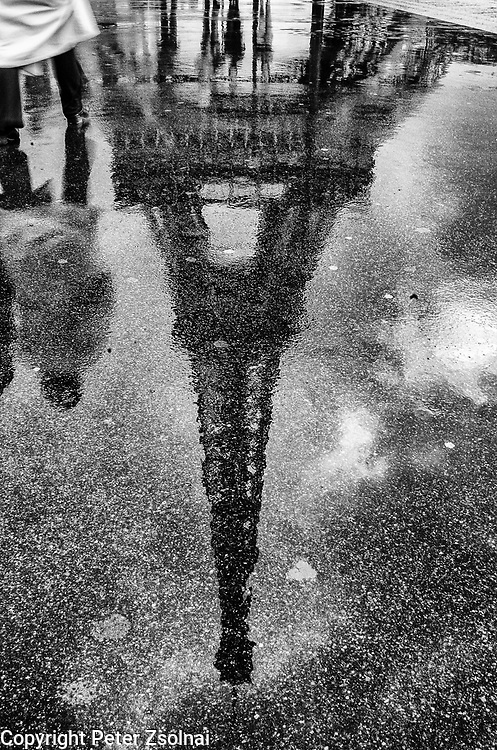 A pedestrian walks by the Eiffel tower in Paris, France.