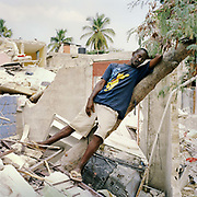 "Livis, leaning against a tree at his neighbour Jocelyn's home near Cham de Mars,  Port au Prince. He is helping Jocelyn to rescue his belongings. Livis was not affected directly, he did not lose any family himself,  but his experiences were similar to those of many Haitians living in central Port Au Prince.  He is a Winnie the Pooh fan and reads it to his five children. He says, ""If you're excited what is the point? You have no choice but to be calm. Captured in my mind are the scenes immediately after the earthquake: the collapsed buildings, the dead bodies and worst of all the cries for help from those under the debris. The cries that would go unanswered until eventually they stopped. They cried but we couldn't help"""