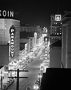 Y-481214-01. Night view of SW Broadway from the Oregonian building, Paramount and Broadway theatres. December 14, 1948