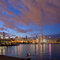 Chicago Skyline seen from the museum campus by the Planetarium on Lake Michigan with person taking self-portrait photo in foreground during October's, Breast Cancer Awareness Month,