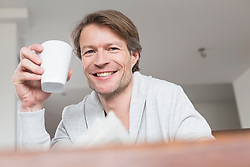 Portrait of mature man holding coffee cup, close up