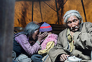 A grandmother and her granddaughter share a tender moment, as her husband sits nearby. Puga, Ladakh