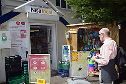 Social distancing in place outside Manorbier Stores, Pembrokeshire, South Wales during Covid pandemic, July 2021. MR