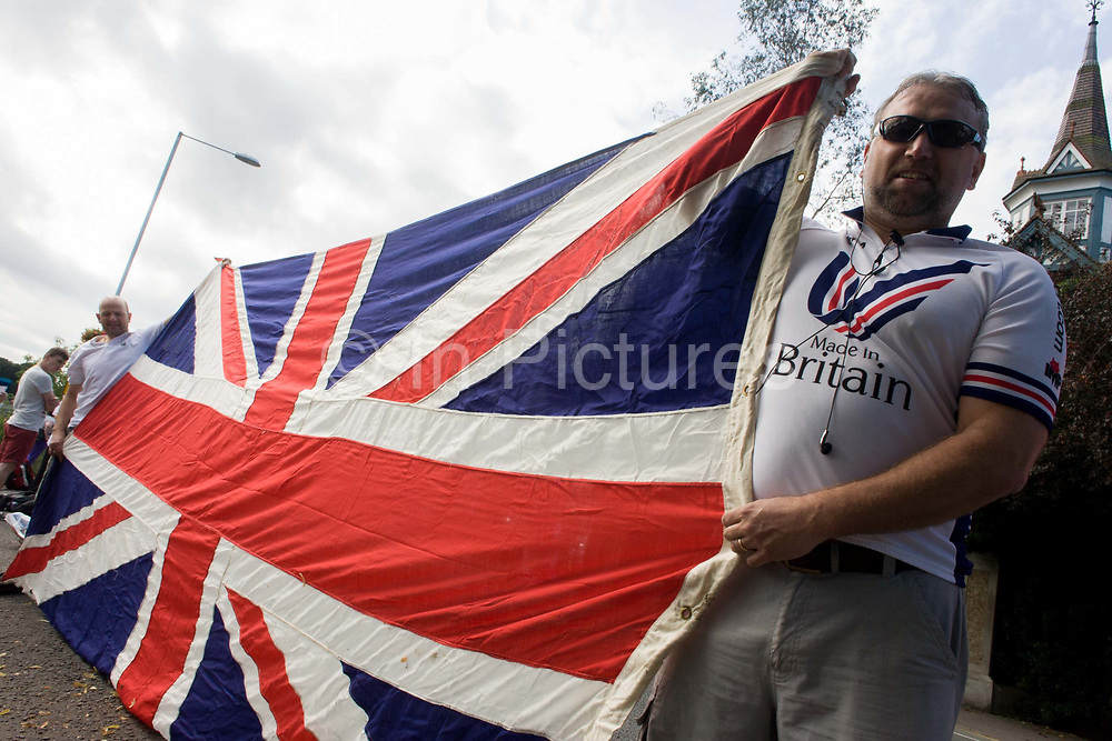 Spectators stretch their 4 metre long union jack flag <br /> on the first day of competition of the London 2012 Olympic 250km mens' road race. Starting from central London and passing the capital's famous landmarks before heading out into rural England to the gruelling Box Hill in the county of Surrey. Local southwest Londoners lined the route hoping for British favourite Mark Cavendish to win Team GB first medal but were eventually disappointed when Kazakhstan's Alexandre Vinokourov eventually won gold.
