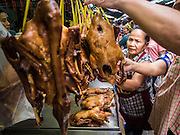 28 AUGUST 2015 - BANGKOK, THAILAND: People buy stewed ducks and chickens to be used as offerings for the ghosts on Hungry Ghost Day in Bangkok's Chinatown. Mahayana  Buddhists believe that the gates of hell are opened on the full moon of the seventh lunar month of the Chinese calendar, and the spirits of hungry ghosts allowed to roam the earth. These ghosts need food and merit to find their way back to their own. People help by offering food, paper money, candles and flowers, making merit of their own in the process. Hungry Ghost Day is observed in communities with a large ethnic Chinese population, like Bangkok's Chinatown.     PHOTO BY JACK KURTZ