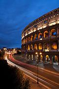 The Roman Coliseum illuminated at dusk as traffic passes by on Via dei Fori Imperiali, Rome, Lazio, Italy.
