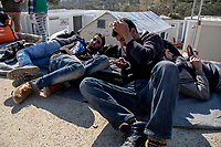 MYTILINI, GREECE - FEBRUARY 09: Refugees rest on the ground while waiting for registration at the Moria refugee camp on February 09, 2015 in Mytilini, Greece. After travelling for more than two hours crossing the Aegean sea, refugees are picked up by buses run by UNHCR and transferred to the Moria refugee camp where they have to register their names. As thousands of refugees arrive everyday in Lesvos, queues for registration can take up to two days. In the camp several international organisations provide assistance to the refugees as food, medical assistance, blankets and clothes among other items and services. Photo: © Omar Havana. All Rights Are Reserved