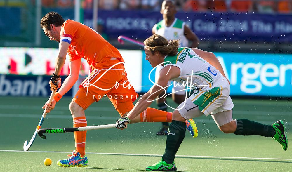 DEN HAAG -  Robert van der Horst is te snel voor Jonathan Robinson.  de wedstrijd tussen de mannen van Nederland en Zuid Afrika in het WK hockey 2014.  ANP KOEN SUYK