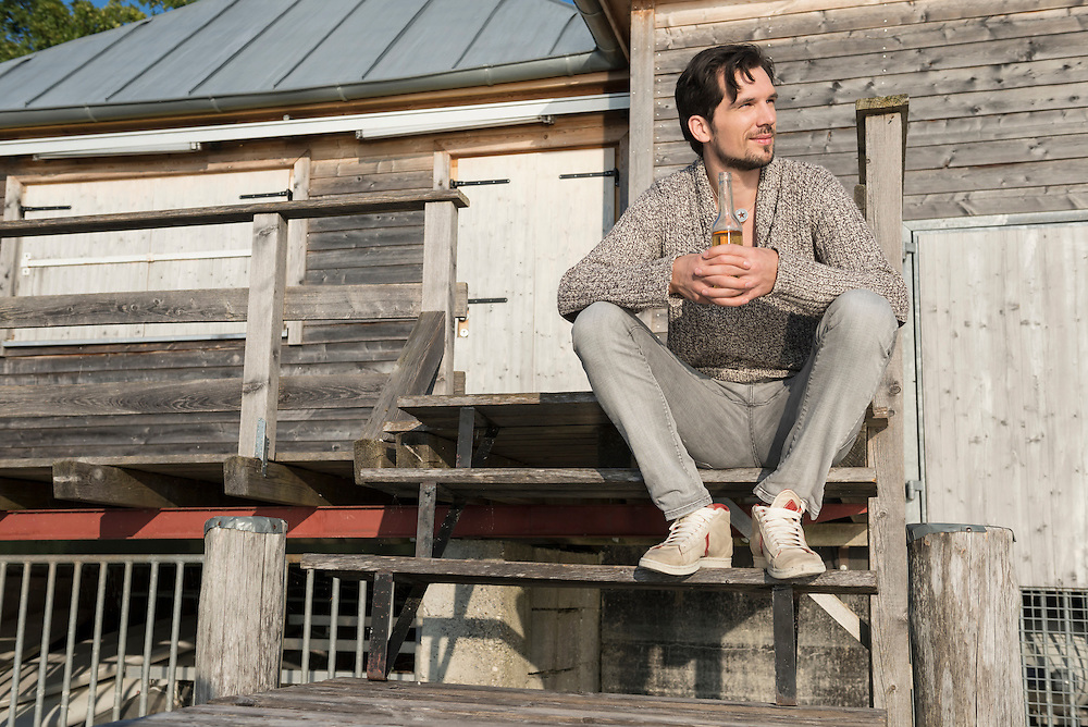 Man sitting drinking beer wooden steps relaxing