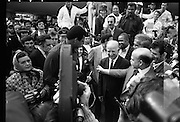 Muhammad Ali In Dublin..1972..11.07.1972..07.11.1972..11th July 1972..Prior to his fight against Al 'Blue' Lewis at Croke Park, Dublin, former World Heavyweight Champion, Muhammad Ali arrives at Dublin Airport..The fight was part of his build up for for a championship fight against the current World Champion, 'Smokin' Joe Frazier. Ali had been stripped of the title partly due to his refusal to join the American military during The Vietnam War, which he had opposed...Photo of Muhammad Ali being mobbed by fans and the media on the tarmac at Dublin Airport. Included in the picture are some members of The Emerald Girls Pipe Band.
