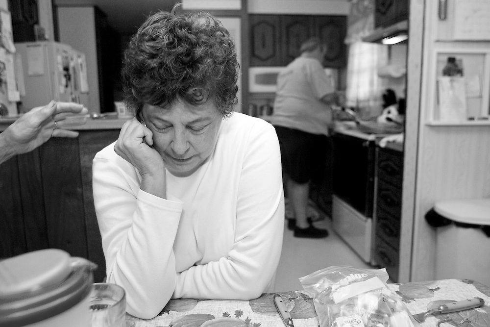 KILLINGWORTH, CT - 23 OCTOBER 2007 -112008JT11-.Marie Tyrrell fights the urge to sleep while sitting at the dinner table as her husband Paul prepares dinner in their double wide mobile home in Killingworth on Oct. 23, 2007. At left is the helping hand of Marie's sister, Claire Baril. Marie had begun her fourth round of chemo in September 2007, and the side effects left her fatigued and barely able to walk. .Josalee Thrift / Republican-American