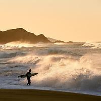 A surfer prepares to take to the sea at Johanna Beach, VIC