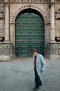 Old man walking by the main entrance to the  Santa Maria de Jesus church in Cuzco, Peru.