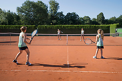 Young girls playing tennis on a sunny day, Bavaria, Germany