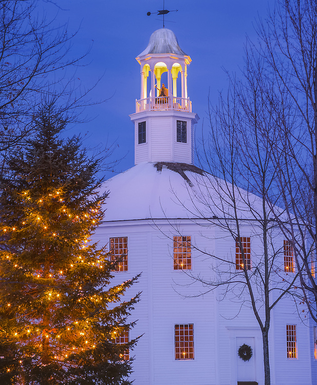 Historic Round Church, 16 sided, 1812, white christmas lights hanging on tree, candles in windows at dusk, Richmond, VT