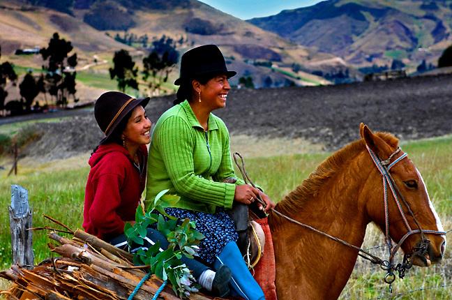 Ecuador, Ingapirca, Girls on horseback collecting wood for the home fires