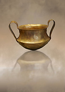 Two handled Mycenaean gold bowl cup from the Kakovatos tholos tomb, Trifylia, Greece. National Archaeological Museum Athens. <br /> <br /> Kakovatos is a significant site of the early Mycenaean period of Greece (c. 16th to 15th century BC) on the west coast of the Peloponnese (Zacharo, Nomos Elis) and became widely known through the excavations of three large tholos tombs by Wilhelm Dörpfeld in 1907–1908. .<br /> <br /> If you prefer to buy from our ALAMY PHOTO LIBRARY  Collection visit : https://www.alamy.com/portfolio/paul-williams-funkystock/mycenaean-art-artefacts.html . Type -   Athens    - into the LOWER SEARCH WITHIN GALLERY box. Refine search by adding background colour, place, museum etc<br /> <br /> Visit our MYCENAEN ART PHOTO COLLECTIONS for more photos to download  as wall art prints https://funkystock.photoshelter.com/gallery-collection/Pictures-Images-of-Ancient-Mycenaean-Art-Artefacts-Archaeology-Sites/C0000xRC5WLQcbhQ