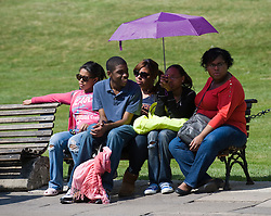 © licensed to London News Pictures. 19/04/2011.  Windsor, UK. A group of young people use an umbrella to shelter from the sunshine in Windsor, Berkshire as temperatures in the UK hit 25 degrees. Please see special instructions for usage rates. Photo credit should read Ben Cawthra/LNP