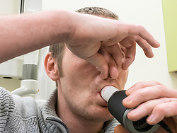 A smoker having a lung capacity test, know as Spirometry.