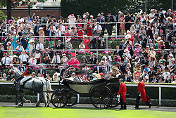 Queen Elizabeth II and The Duchess of Cornwall arriving with The Prince of Wales and Lord Fellowes as racegoers watch in the parade ring during day two of Royal Ascot at Ascot Racecourse.