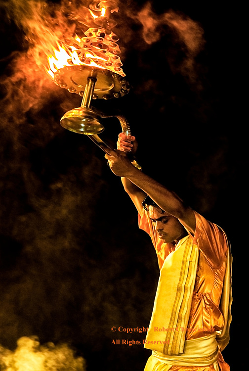 Hindu Fire: The Aarti Ceremony performed by a young Hindu priest, using an elaborate fire bearing vessel, at Assi Ghat, Varanasi India.