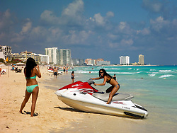09 Feb 2014. Cancun, Mexico.<br /> Tourists pose with a jet on the tourist beach at Isla Cancun along the Zona Hotelera on the Carribean Sea. <br /> Photo; Charlie Varley/varleypix.com