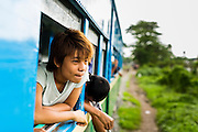 15 JUNE 2013 - YANGON, MYANMAR:  Passengers lean out of the windows of the Yangon Circular Train. They Yangon Circular Railway is the local commuter rail network that serves the Yangon metropolitan area. Operated by Myanmar Railways, the 45.9-kilometre (28.5mi) 39-station loop system connects satellite towns and suburban areas to the city. The railway has about 200 coaches, runs 20 times and sells 100,000 to 150,000 tickets daily. The loop, which takes about three hours to complete, is a popular for tourists to see a cross section of life in Yangon. The trains from 3:45 am to 10:15 pm daily. The cost of a ticket for a distance of 15 miles is ten kyats (~nine US cents), and that for over 15 miles is twenty kyats (~18 US cents). Foreigners pay 1 USD (Kyat not accepted), regardless of the length of the journey.     PHOTO BY JACK KURTZ
