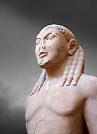 Archaic Ancient Greek marble statue of a Kouros, one of the Twins of Argos sculpted in the Argos archaic workshop circa 580 BC, Delphi National Archaeological Museum.   Against grey.