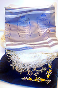Tallit and an elaborated decorated talit bag, Tifillin are either of two boxes containing Biblical verses and black, leather straps attached to them which are used in rabbinic Jewish prayer. They are an essential part of morning prayer services, and are worn on a daily basis (except the Sabbath and festivals) by religious Jewish males above the age of 13 years