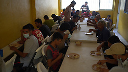 In a migrant refuge in Tapachula, Mexico, men eat a meal.