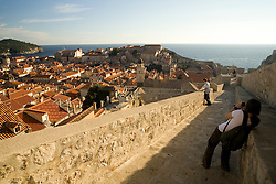 Europe, Croatia, Dalmatia, Dubrovnik. Female tourist photographing Dubrovnik from city walls (built 10th century).  Island of Lokrum is in distance. The historic center of Dubrovnik is a UNESCO World Heritage site.