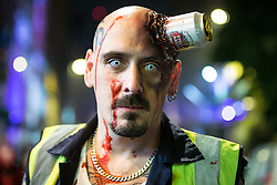 © Licensed to London News Pictures . 01/11/2015 . Manchester , UK . A man with a can of Stella Artois embedded in his head . Halloween revellers , wearing make up and costumes , out and about in Manchester City Centre . Photo credit : Joel Goodman/LNP