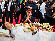 12 OCTOBER 2104 - BANG BUA THONG, NONTHABURI, THAILAND: A woman wails while praying at the funeral rites for Apiwan Wiriyachai at Wat Bang Phai in Bang Bua Thong, a Bangkok suburb, Sunday. Apiwan was a prominent Red Shirt leader, member of the Pheu Thai Party of former Prime Minister Yingluck Shinawatra, and a member of the Thai parliament. The military government that deposed the elected government in May, 2014, charged Apiwan with Lese Majeste for allegedly insulting the Thai Monarchy. Rather than face the charges, Apiwan fled Thailand to the Philippines. He died of a lung infection in the Philippines on Oct. 6. The military government gave his family permission to bring him back to Thailand for the funeral. He will be cremated later in October. The first day of the funeral rites Sunday drew tens of thousands of Red Shirts and their supporters, in the first Red Shirt gathering since the coup.    PHOTO BY JACK KURTZ