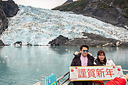 Chinese tourists pose in front of Coxe Glacier, a tidewater glacier in Barry Arm, Harriman Fjord, Prince William Sound near Whittier, Alaska.
