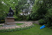 A homeless person rests in a sleeping bag next to the statue of Scottish poet Robert Burns, on 4th May 2017, in London, England.