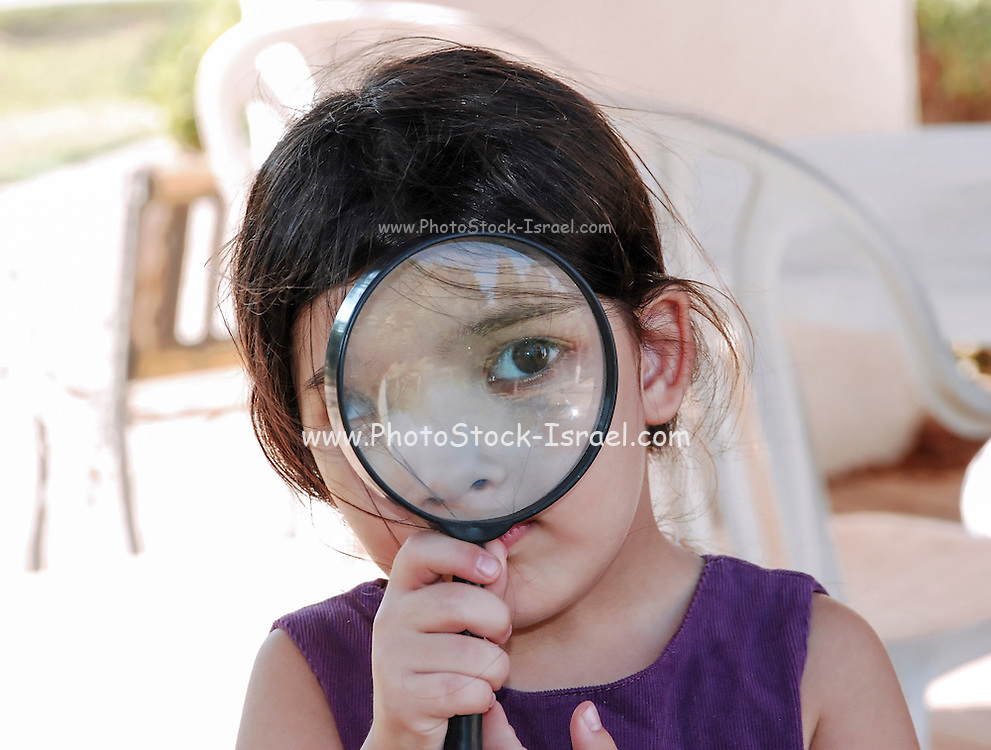 Young girl of four with magnifying glass