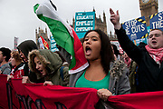 November 21st. Westminster. Demonstration organised by National Union of Students (NUS) against education cuts. A group of students stand shouting in front of Big Ben with placards and a Palestinian flag.
