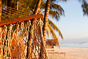A traditional hammock hangs between two palm trees on Paje beach on 3rd December 2008 in Zanzibar, Tanzania. Zanzibar is a small island just off the coast of the Tanzanian mainland in the Indian Ocean. In part due to its name, Zanzibar is a travel destination of mystical reputation, known for its incredible sealife on its many reefs, the powder white coral sand beaches and the traditional cultivation of spices.