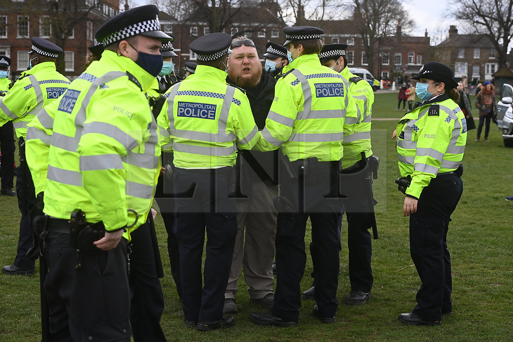 © Licensed to London News Pictures. 06/03/2021. London, UK. An anti-vaccination and anti-lockdown protester is arrested by police officers at a demonstration organised by Jam For Freedom in Richmond.The group is using music to create positive effects and health against the current tier regulations and anti-vaccination for the Covid-19 disease. Photo credit: Ray Tang/LNP